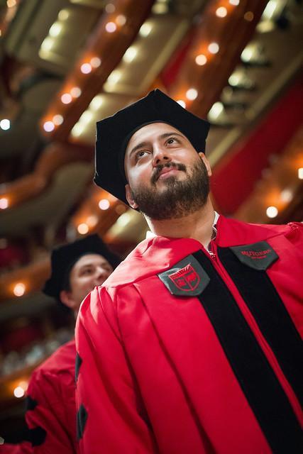 Abo Mahmoud  stands at graduation looking upward