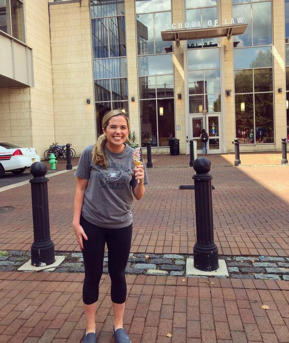 Bridget Devlin stands in front of the Rutgers Law location in Camden holding an ice cream cone.