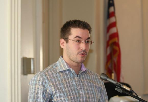 Landon Hacker speaking at a podium