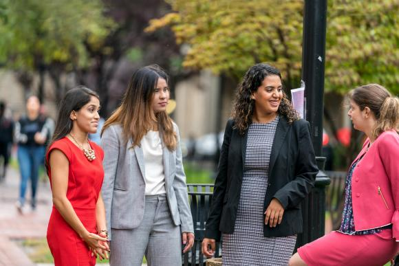 Four women in business clothing stand outside on a grassy campus space.
