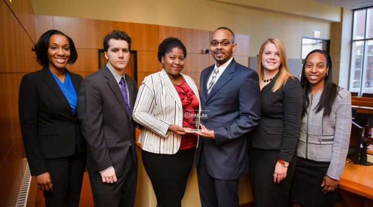 Students from Camden holding an award after a moot court competition.