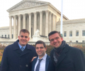 Three law students stand in front of the U.S. Supreme Court on a cold day.